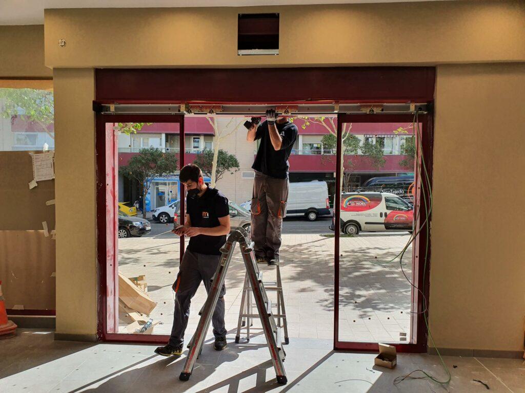 Equipo de Magaiz instalando las nuevas puertas automáticas.